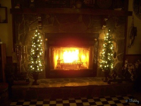 our fireplace and lighted trees on the hearth
