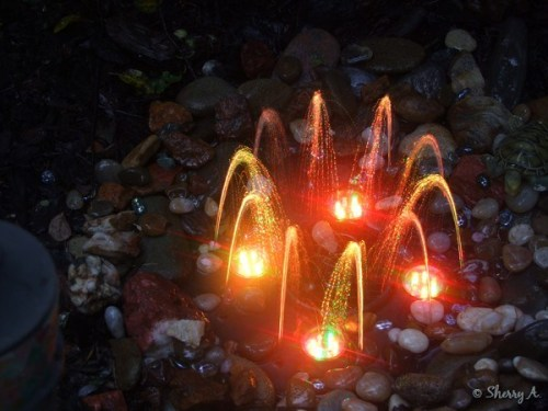 lighted fountain in the secret garden